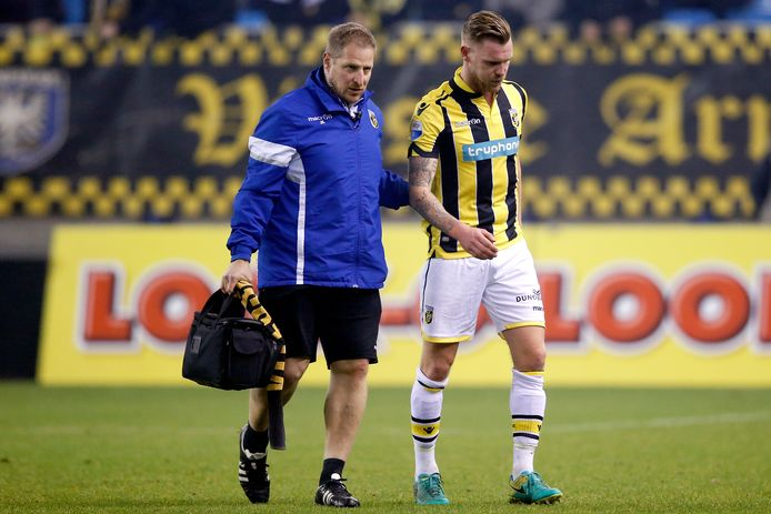 Maikel van der Werff verlaat in bijzijn van fysiotherapeut Jos Kortekaas het veld tegen Willem II.