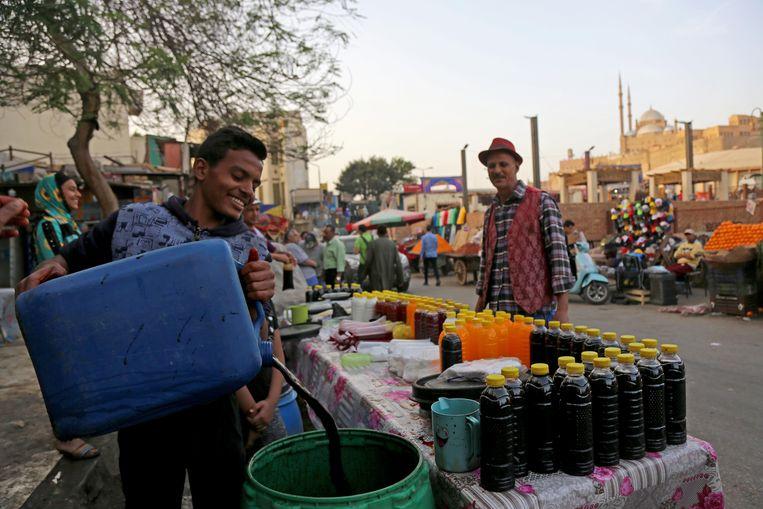 Ramadan-sapjes te koop in een straat in de Egyptische hoofdstad Caïro, vlak voor zonsondergang.   Beeld NurPhoto via Getty Images