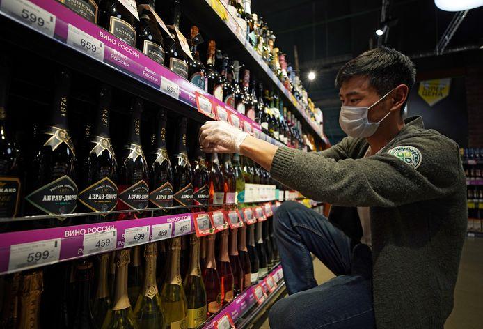 Een winkelmedewerker in Moskou rangschikt flessen Russische 'champagne'.