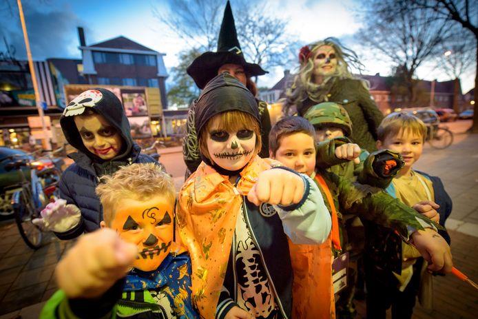 Kinderen verkleed in griezelpakken trekken tijdens Halloween in de avond samen met hun ouders verkleed langs de deuren voor 'trick or treat'.