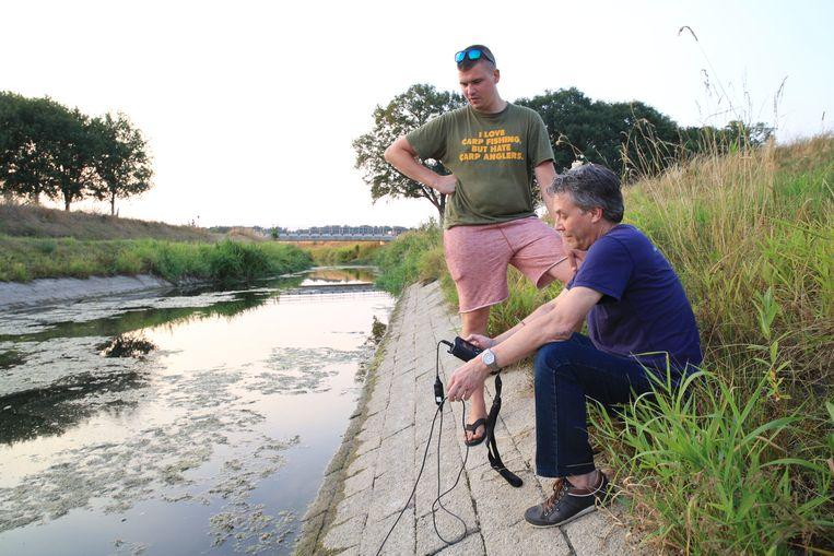 In gesprek met een karpervisser die helpt vissen over te zetten die door zuurstoftekort dreigen dood te gaan. Beeld Arie Kievit