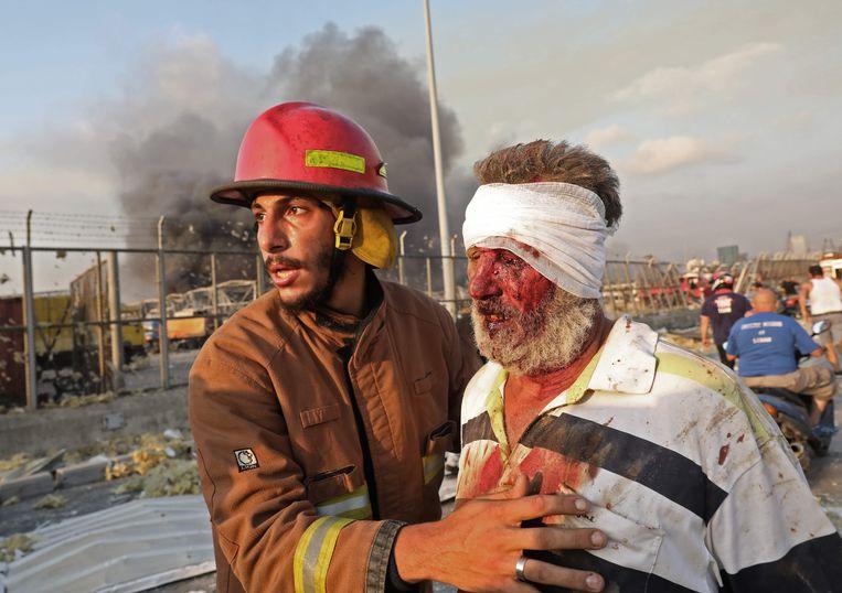 Een brandweerman verzorgt een gewonde man na de klap. Beeld AFP