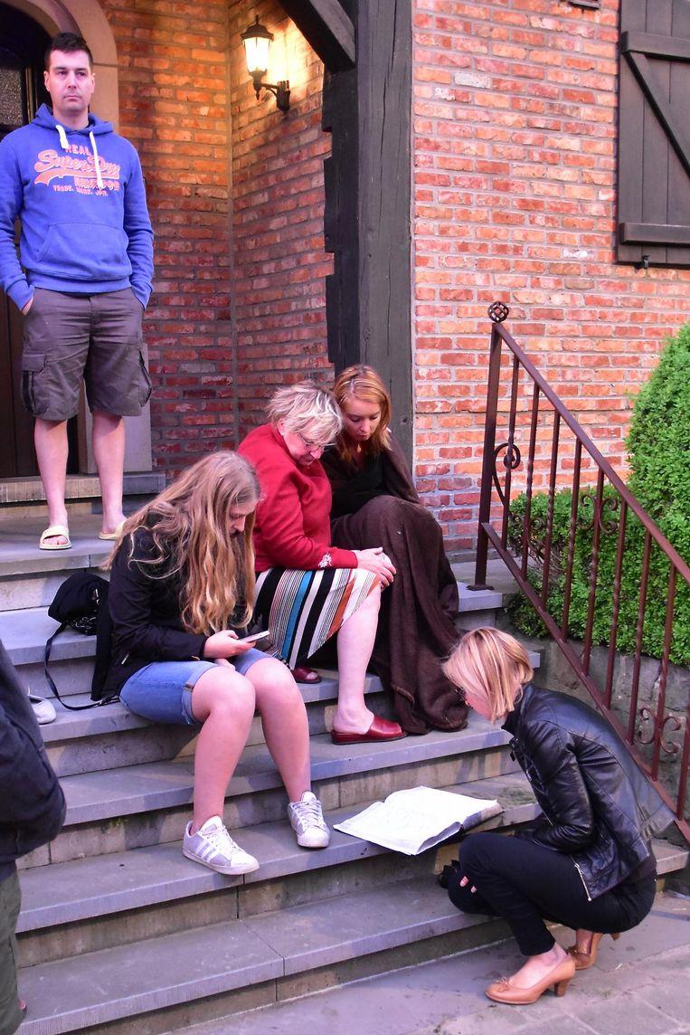 Laura Soetens (rechts, zittend op de trap) is erg onder de indruk. Haar zus Sarah (gehurkt) bladert in het reservatieboek, dat door de brandweer kon worden gered. Rechtstaand: overbuur Niek Avet.