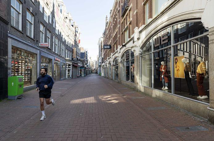 Een uitgestorven Kalverstraat. Vanwege de coronacrisis is het stil op de normaal drukke pleinen en winkelstraten van de hoofdstad.