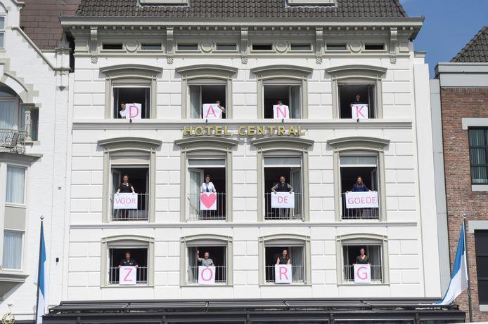 Medewerkers van hotel Central met letters achter de ramen van het gebouw aan de Markt om  zorgmedewerkers en vrijwilligers van het Jeroen Bosch Ziekenhuis te bedanken.