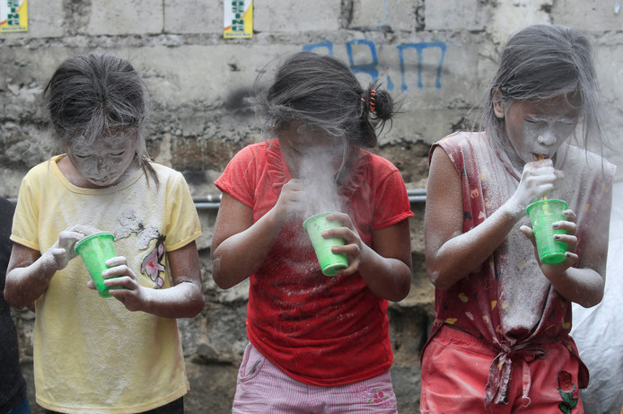 In Paranaque City, op de Filipijnen, vieren drie meisjes het feest van de beschermheilige Santa Rita de Cascia. Ze blazen in met poeder gevulde bekertjes. Foto Romeo Ranoco