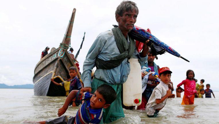 Een Rohingya-vluchteling houdt een kind bij de arm nadat ze via de zee zijn gevlucht naar Bangladesh. Beeld reuters