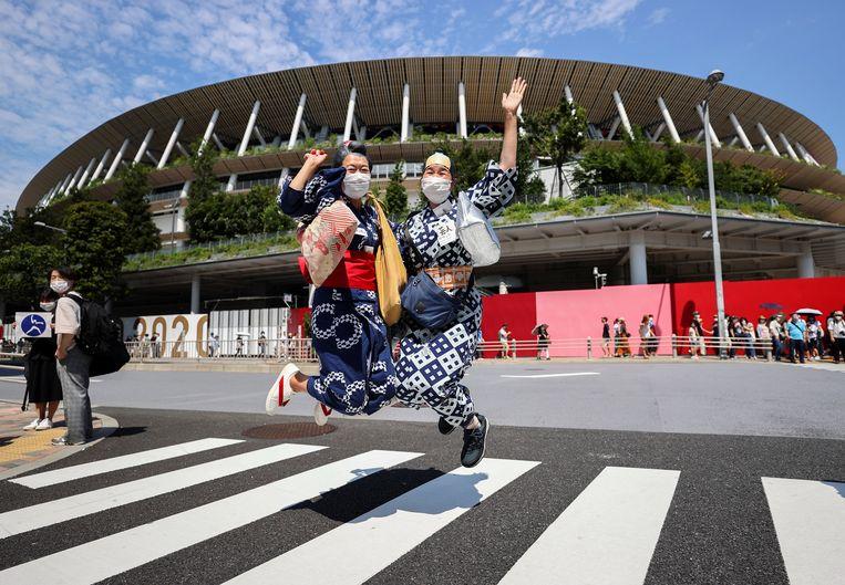 Japanse vrouwen in traditionele Yukata-kimonos voor het olympisch Stadion in Tokio.  Beeld Reuters