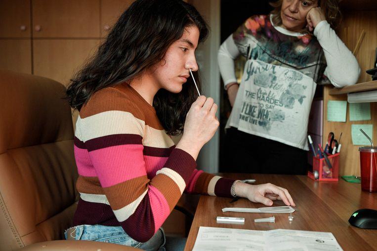 Een meisje gebruikt een zelftest. Beeld AFP
