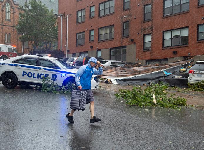 Een man maakt zich uit de voeten bij een appartementencomplex in Halifax in het Canadese Nova Scotia, waar een deel van het dak door orkaat Dorian werd weggeblazen en op een aantal geparkeerde auto's terechtkwam. De bewoners van het gebouw werden geëvacueerd.