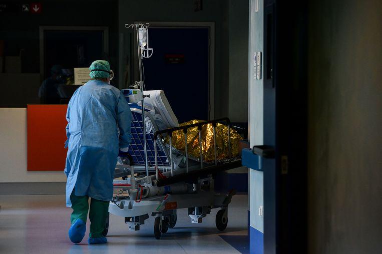 Een ziekenhuismedewerker ontfermt zich over een coronapatiënt in Brescia. Beeld AFP