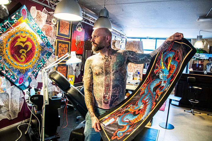 Tatoeëerder Darko Groenhagen van Oneness tattoo studio in Tilburg, toont een schildering die hij maakte van een Japanse draak.