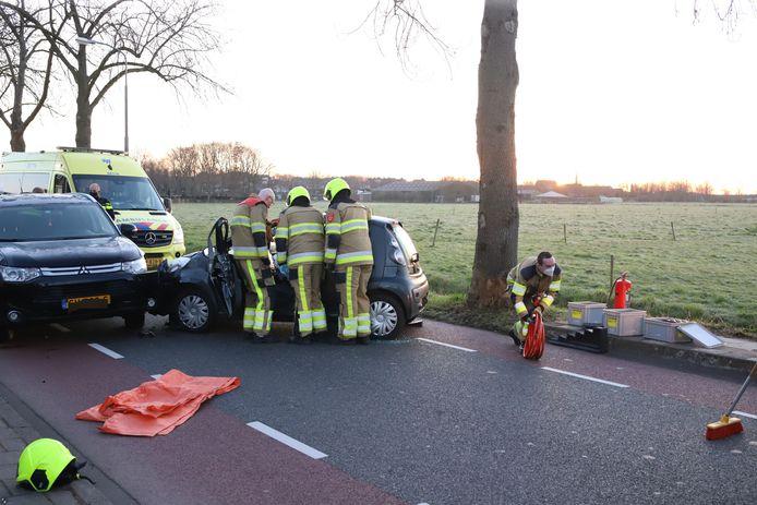 De brandweer bevrijdt de vrouw uit haar auto in Asperen.