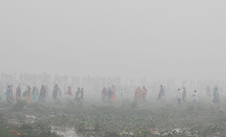 Inwoners van Delhi aanbidden de zonnegod tijdens het religieuze Hindoestaanse festival Chatth Puja.  Beeld REUTERS