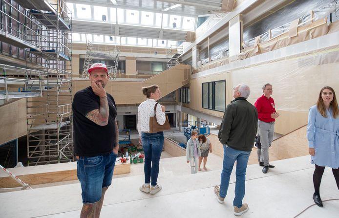 Oud-leerling Almar te Nijenhuis (links) kijkt geïnteresseerd rond in het atrium van het Christelijk Lyceum Veenendaal, rechts architecte Loes Thijssen.
