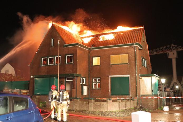 De vlammen slaan uit het dak van de oude havenmeesterswoning op Urk.