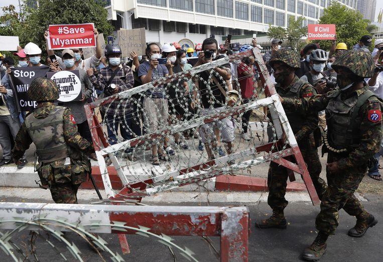 Het leger zette maandag een barricade op nabij de Centrale Bank in Yangon. Het protest tegen de staatsgreep in het land groeit en demonstaties in Yangon keren dagelijks terug, ondanks hard ingrijpen van het leger. Beeld EPA