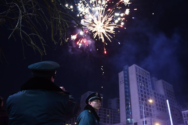 Veiligheidsagenten kijken toe hoe mensen vuurwerk afsteken voor het Chinees Nieuwjaar.