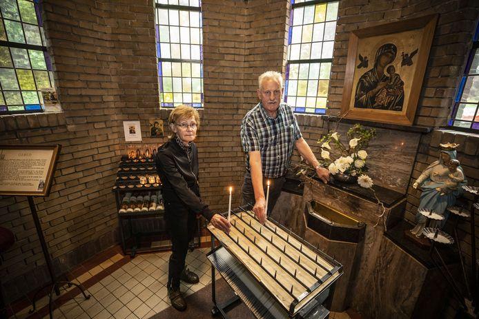 Hoofdkoster Herman Groote Punt en hulpkoster Ans Brummelhuis steken een kaarsje aan in de kapel.