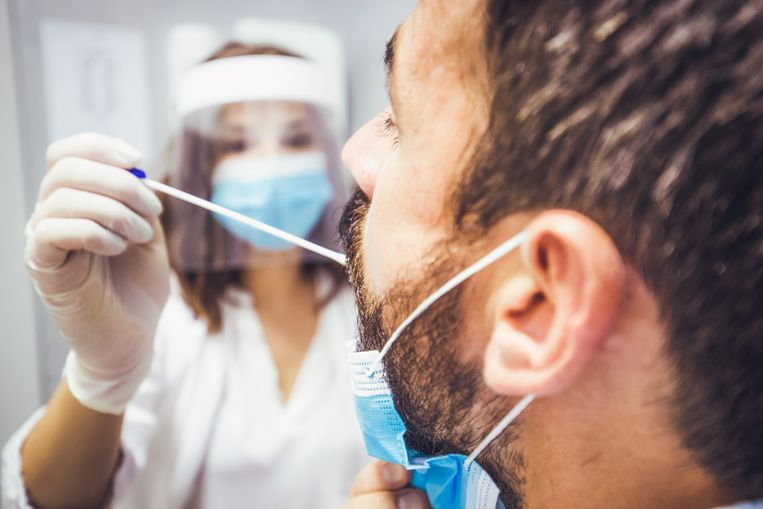 A rear view of a man's head while a doctor is taking a sample of his swab. Both protected with face masks. Beeld Getty Images