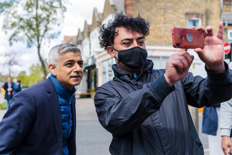 Een man neemt een selfie met Londens burgemeester Sadiq Khan (l.) Beeld EPA