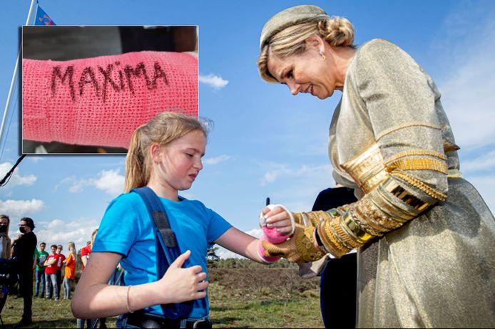 Koningin Máxima zet haar naam op de gipsarm van Marilynn.