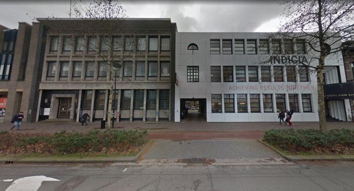 Het monumentale bankgebouw (links) en het Indiciapand met onderdoorgang (rechts). Op de achtergelegen parkeerplaats zou de nieuwbouw gedeeltelijk op buurmans grond zijn geprojecteerd.
