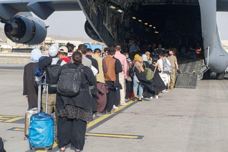 In Kabul stappen mensen in in een Hercules-vrachtvliegtuig van het Amerikaanse leger. Beeld Reuters