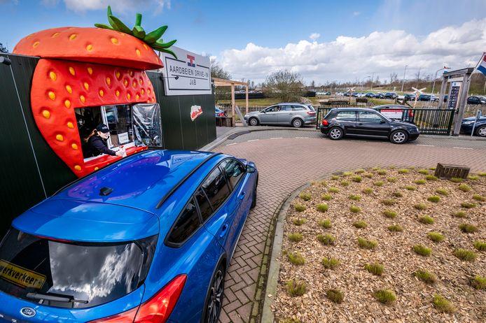Grote drukte bij aardbeien drive-in J&B. Auto's staan in een lange rij te wachten.