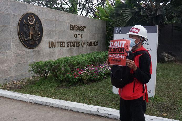 Een demonstrant die protesteert tegen de militaire staatsgreep in Myanmar staat bij de Amerikaanse ambassade.