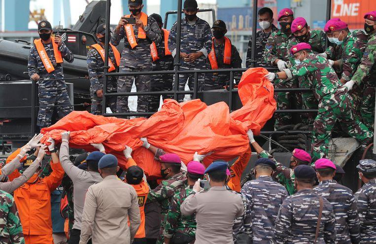 De Indonesische politie en marine sjouwen een zeildoek met daarin de brokstukken van het toestel die in zee zijn gevonden. Beeld AP