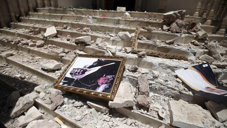 Een portret van koning Salman bin Abdulaziz tussen de brokstukken na een aanval in Sanaa (21 april). Beeld REUTERS
