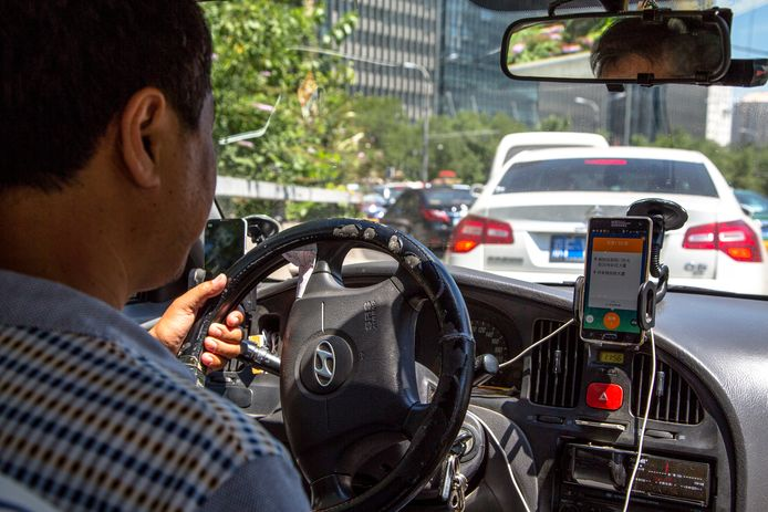 Een taxichauffeur die in Peking de app van Didi gebruikt.