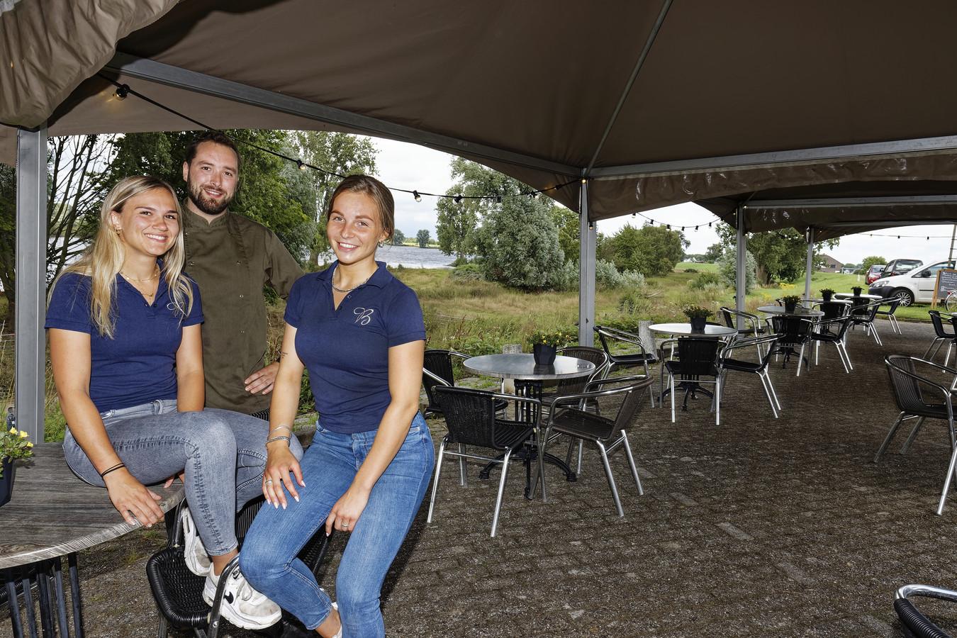 Vlnr: Eva Brekelmans, eigenaar Rens Kemp en Sanne Paloltzka op het terras van De Blauwe Sluis.