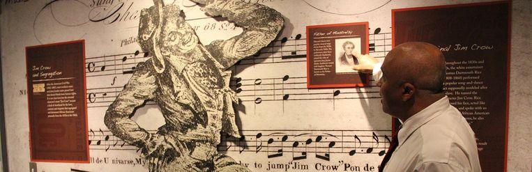 Jim Crow, het verzamelbegrip voor Amerikaans racisme, is van oorsprong een typetje van de witte acteur Thomas Dartmouth Rice (1808-1860), met een zwart gemaakt gezicht en een raar accent. Hier op een afbeelding in het Jim Crow Museum met het bijbehorende lied 'Jump Jim Crow' Beeld Jim Crow Museum