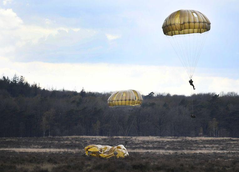 Parachutisten van de landmacht worden tijdens een oefening gedropt boven de Ginkelse Heide.  Beeld ANP