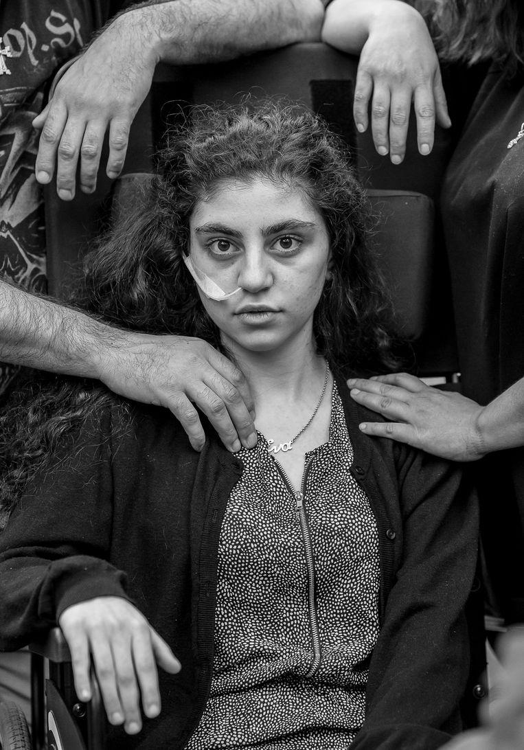 Een 15-jarig Armeens meisje zit in een rolstoel, geflankeerd door haar ouders, in een opvangcentrum voor vluchtelingen in Podkowa Leśna (Polen). Fotograaf Tomek Kaczor won hiermee in de categorie 'Portraits'. Beeld EPA
