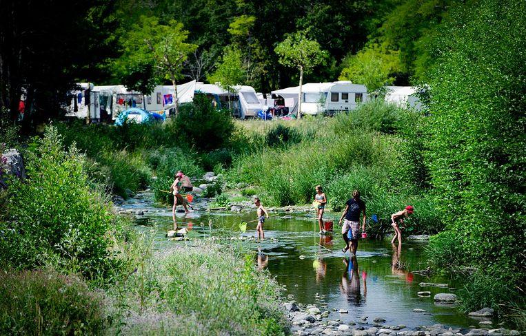Kinderen lopen rond met schepnetje in een riviertje langs een camping in het Franse Villeneuve-de-Berg (Ardeche). Foto ter illustratie. Beeld anp