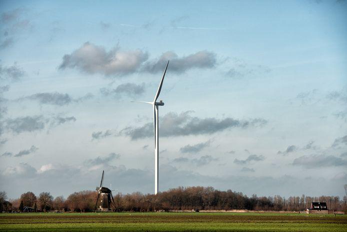 Een van de windturbines bij knooppunt Deil. Links een oude korenmolen.