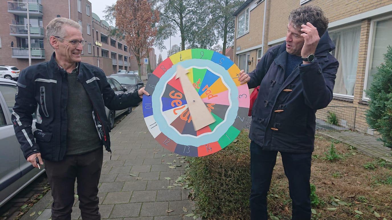 Frans Dix (l) en Alex van der Heijden trekken met het Rad van Geluk kriskras door de Schadewijk.