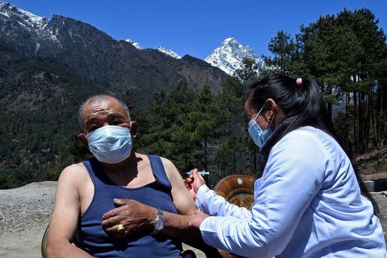 Een man wordt gevaccineerd in de buurt van het plaatsje Lukla, Nepal. Beeld AFP