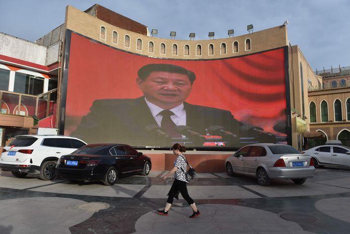 Een groot scherm in de Chinese provincie Xinjiang toont een toespraak van de Chinese president Xi Jinping.