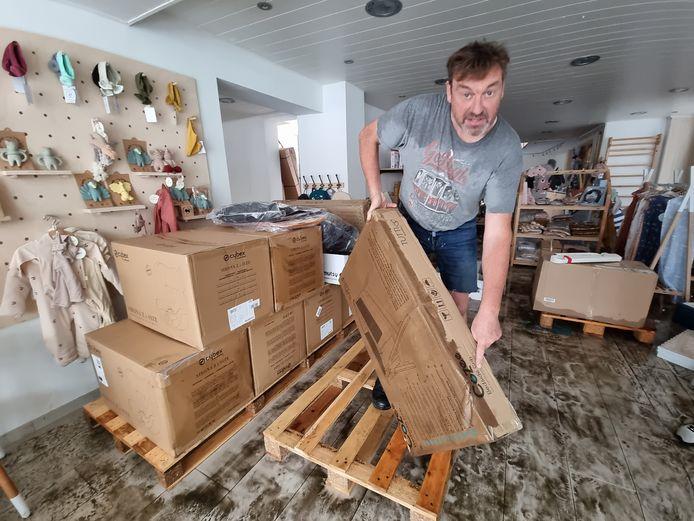 Stefaan Blondeel van Babycenter Verdoodt haalt de door water beschadigde spullen uit de winkel na de onweersbui zondagmiddag in Halle.