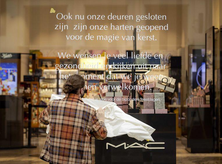 Medewerkers plakken stickers over de tijdelijk winkelsluiting op het raam van de Bijenkorf in Amsterdam nadat premier Rutte in december een nieuwe lockdown aankondigde. Beeld ANP