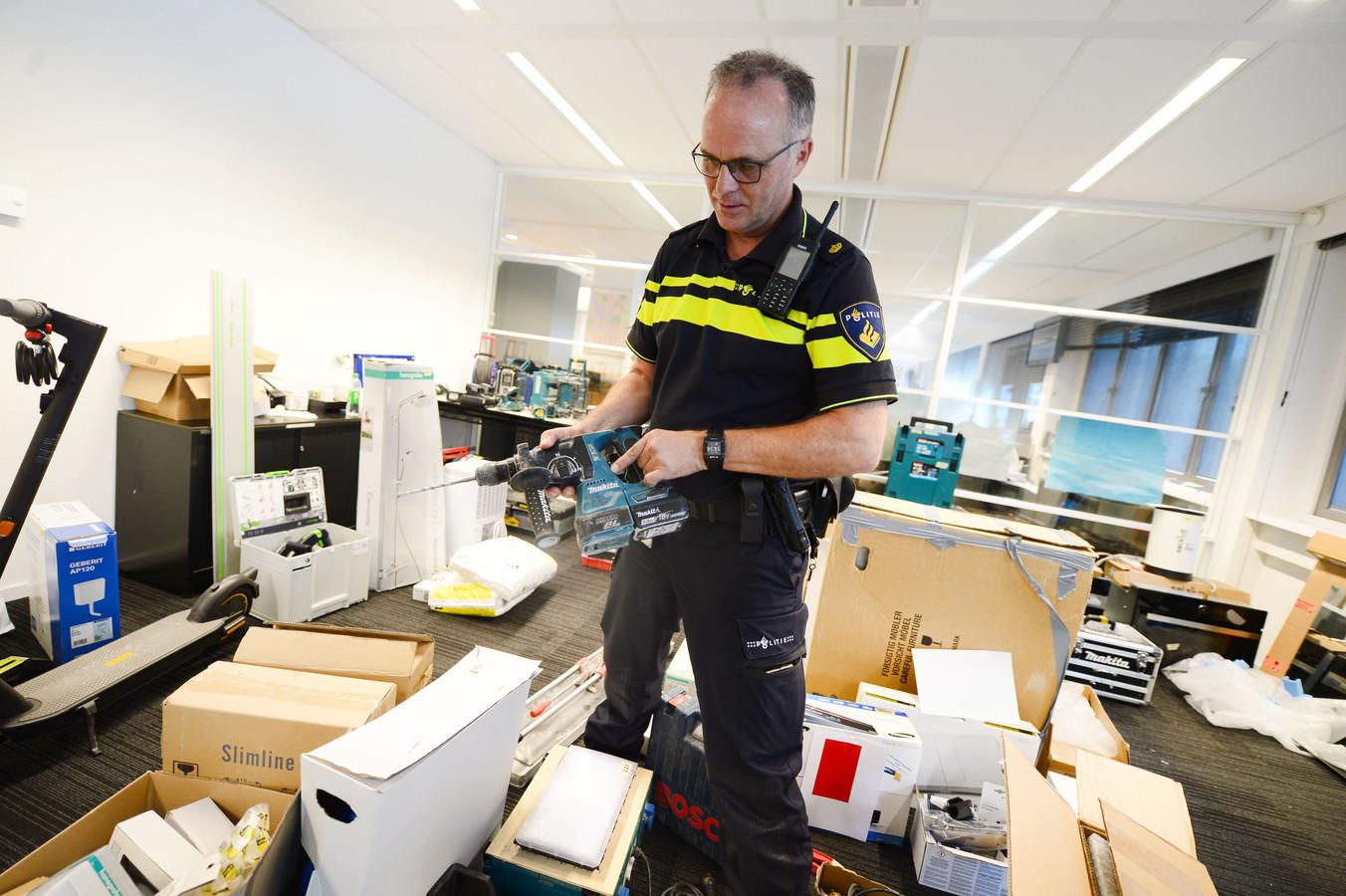 Teamleider Henk Schuler van de politie Almelo tussen de in beslag genomen goederen.