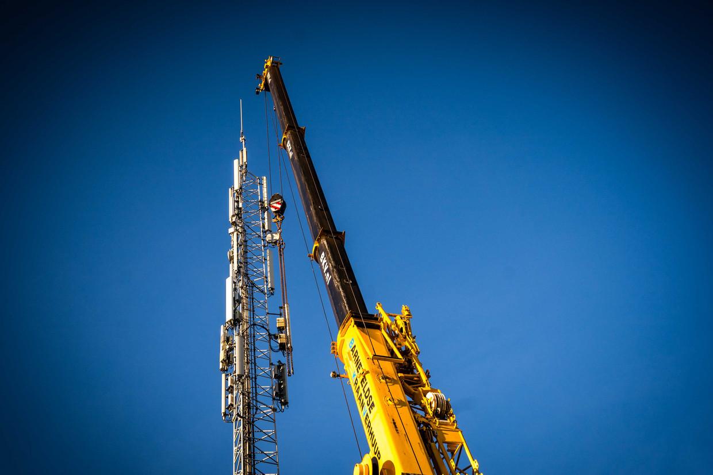 Monteurs aan het werk bij een zendmast voor mobiele netwerken in Nuenen die door een brand zwaar beschadigd is geraakt.