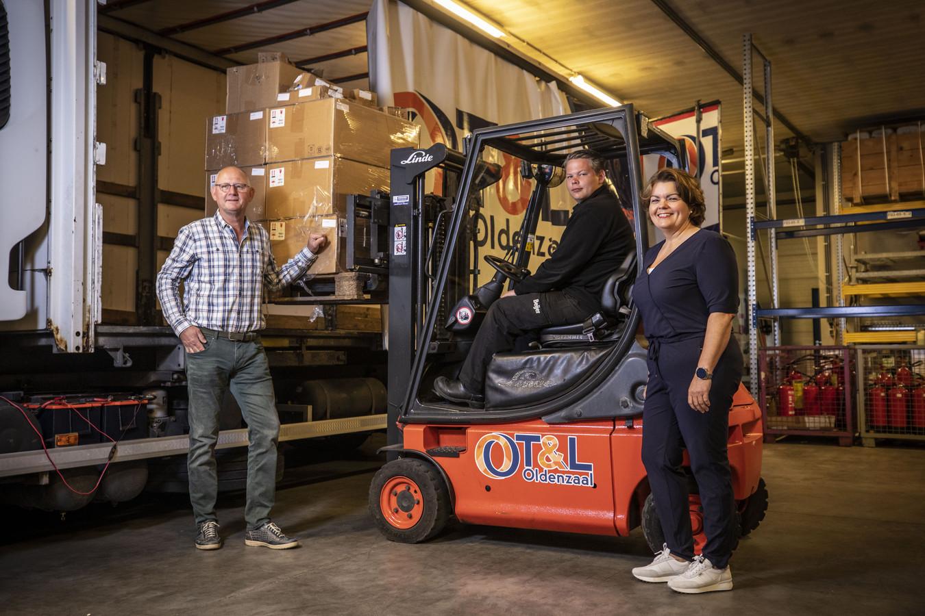 In de praktijkhal zien bestuursvoorzitter Jan Bergman van het Coöperatieve Opleidingscentrum Transport & Logistiek Oldenzaal en Lisette Boetzkes van het OT&L hoe Wout Peters uit Lattrop geroutineerd een pallet vol dozen in de vrachtwagen laadt.