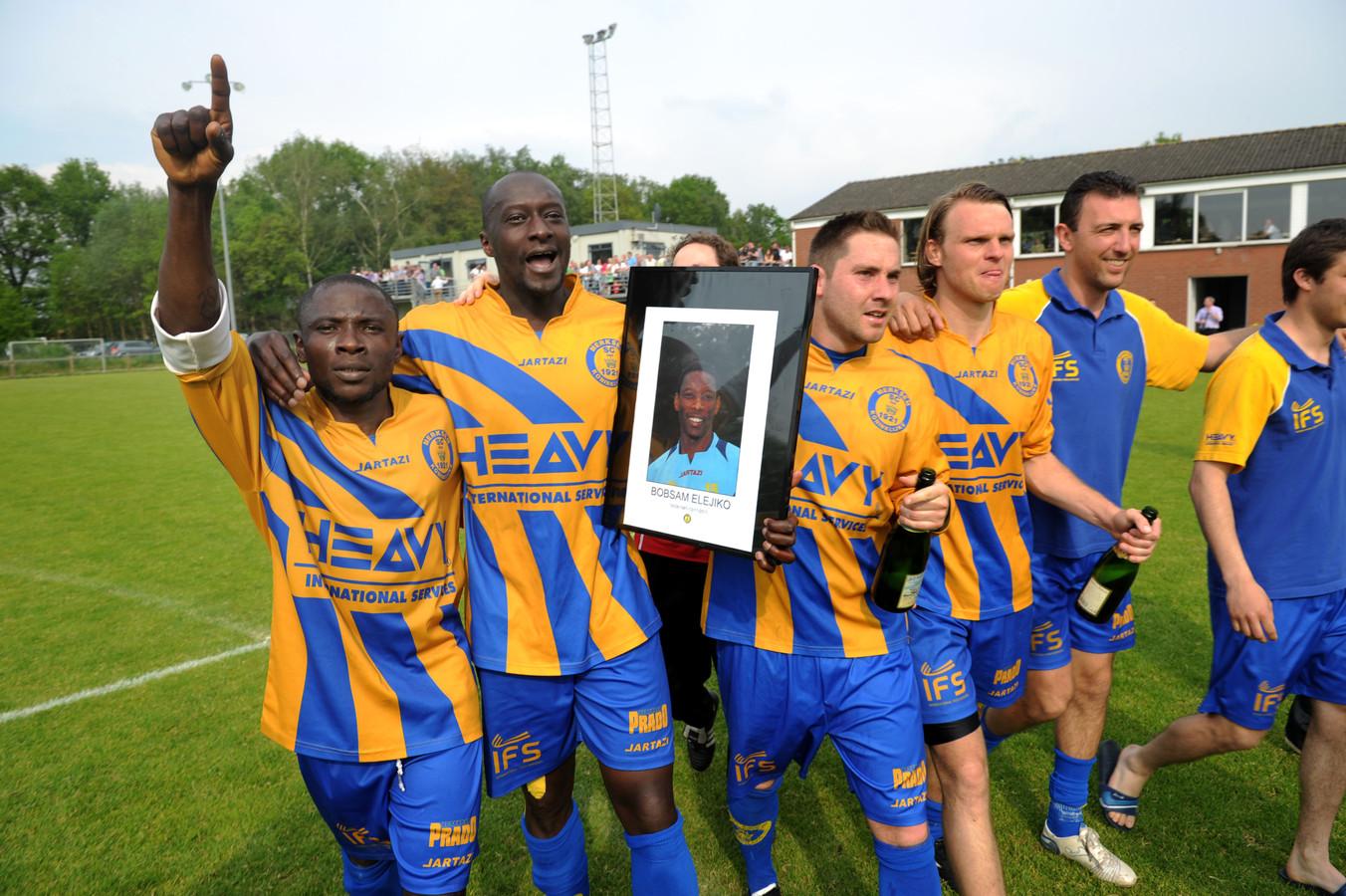 De spelers van Merksem vieren de promotie in 2012, in gezelschap van het portret van de betreurde Bobsam Elejiko.