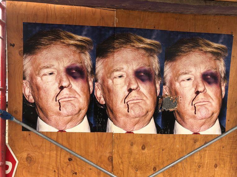 Een bewerkte poster in Beverly Hills toont Amerikaans president Donald Trump met blauw oog en bloedneus.  Beeld Photo News