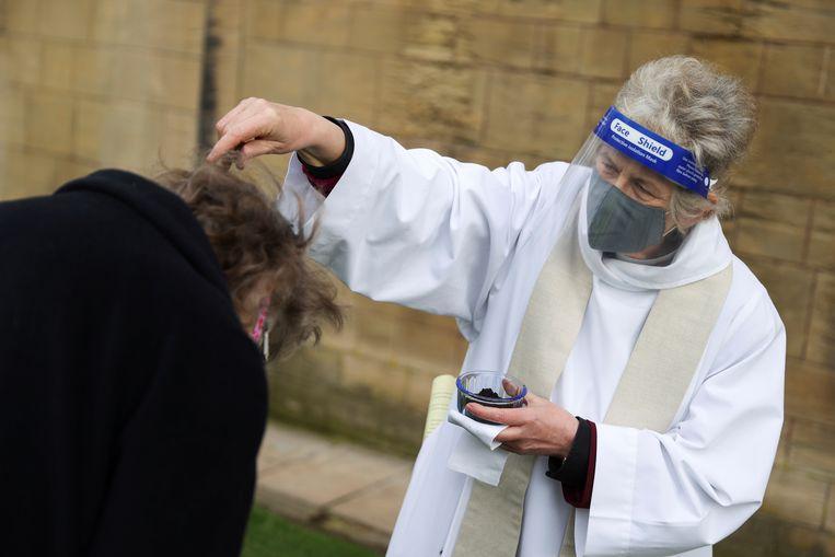 Een gelovige in Nottinghamshire in Groot-Brittannië krijgt een askruisje in de buitenlucht. Beeld REUTERS